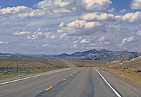 """""""THAT OLD HIGH ROAD GOES ON FOREVER""""   Heading west on US287 in Wyoming.  Note Vulture-like bird soaring in front of 2nd big cloud (center). Only vehicle in sight is yellow farm machine on left."""