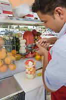 Male street vendor preparing fruit salad