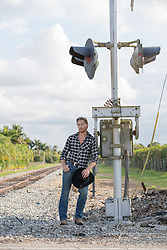 cowboy holding his hat and leaning against a railroad track signal