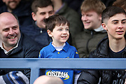 Young Fan wearing AFC Wimbledon top and smiling whilst stood in stand during the EFL Sky Bet League 1 match between AFC Wimbledon and Bolton Wanderers at the Cherry Red Records Stadium, Kingston, England on 7 March 2020.