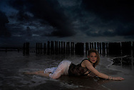 Shipwrecked.  A beautiful girl washed up on the shore after a storm.  A fantasy art image.