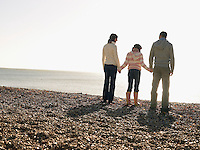 Family of three holding hands standing on beach back view