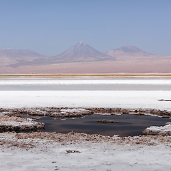 The saltflats of the Tebinquinche lagoon create a surreal effect. On the backdrop the Andes mountain range and with almost 6000 meters volcano Licancabur on the background, Tebinquinche, Chile.