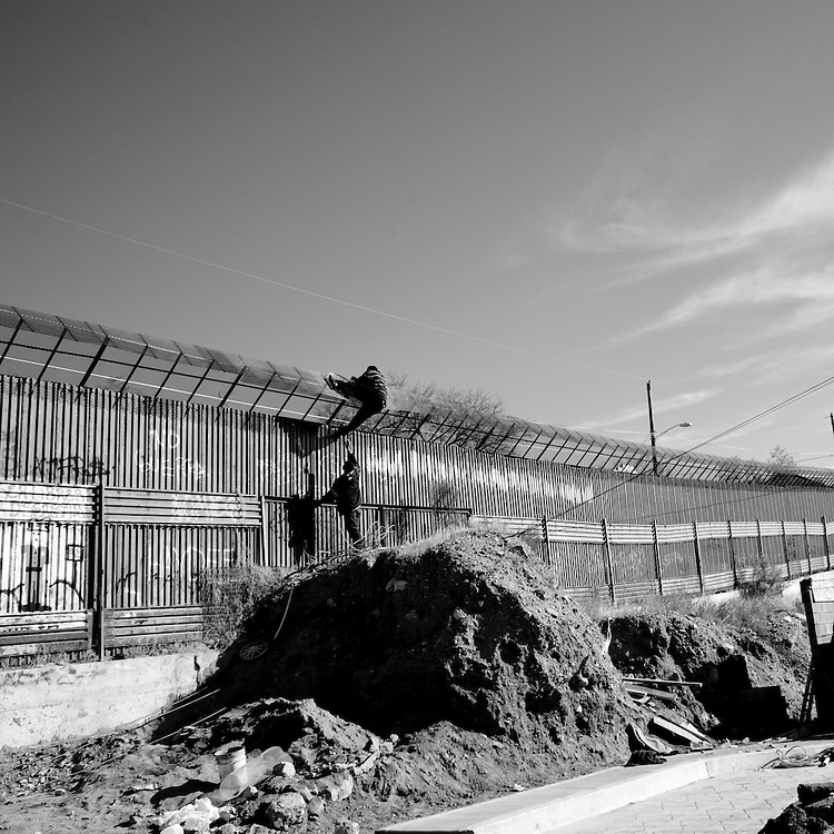 Two men climb over the fence separating the United States and Mexico in Nogales, Sonora, Mexico, on Friday, Feb. 1, 2008.