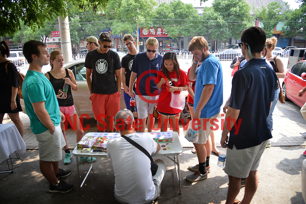 Poole College of Management Study Abroad students watch a street artist work in Beijing.