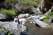 Woman sitting on rock by rapids in the channel of the River Rio Poqueira gorge valley, High Alpujarras, Sierra Nevada, Granada Province, Spain