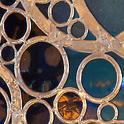 Detail of a stained glass window with many circles in the leadwork, in the Bell tower room themed 'Le Merveilleux' or The Supernatural, first floor, in Le Tresor de la Cathedral d'Angouleme, in Angouleme Cathedral, or the Cathedrale Saint-Pierre d'Angouleme, Angouleme, Charente, France. The 12th century Romanesque cathedral was largely reworked by Paul Abadie in 1852-75. In 2008, Jean-Michel Othoniel was commissioned by DRAC Aquitaine - Limousin - Poitou-Charentes to display the Treasure of the Cathedral in some of its rooms, which opened to the public on 30th September 2016. Picture by Manuel Cohen. L'autorisation de reproduire cette oeuvre doit etre demandee aupres de l'ADAGP/Permission to reproduce this work of art must be obtained from DACS.