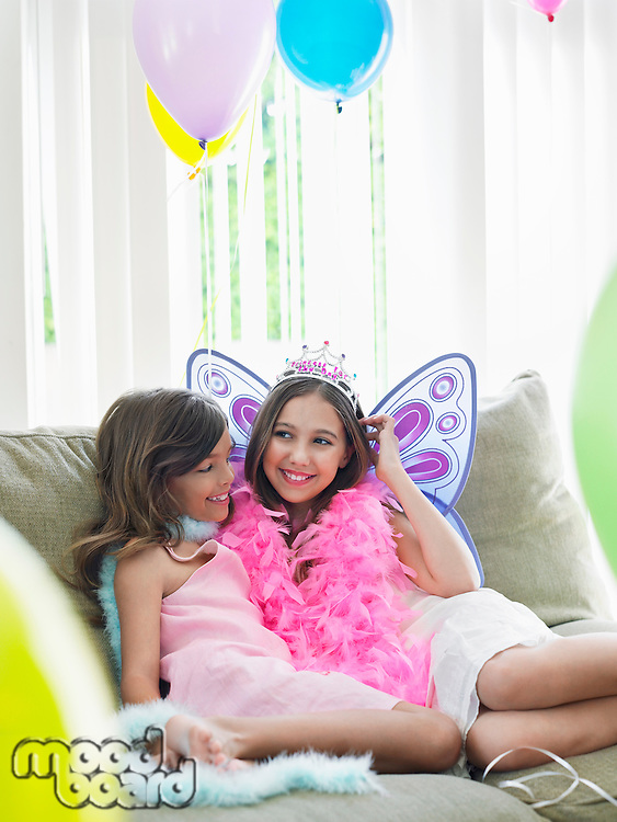 Portrait of two girls (7-9 10-12) sitting on sofa in party costumes