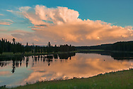 Sunset light in storm clouds over the Yellowstone River with the wake of a white pelican crossing the river,  Yellowstone National Park