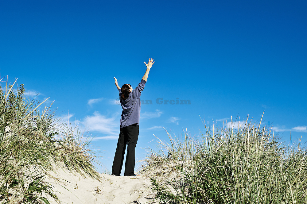 Woman opens her arms in thankful gratitude.