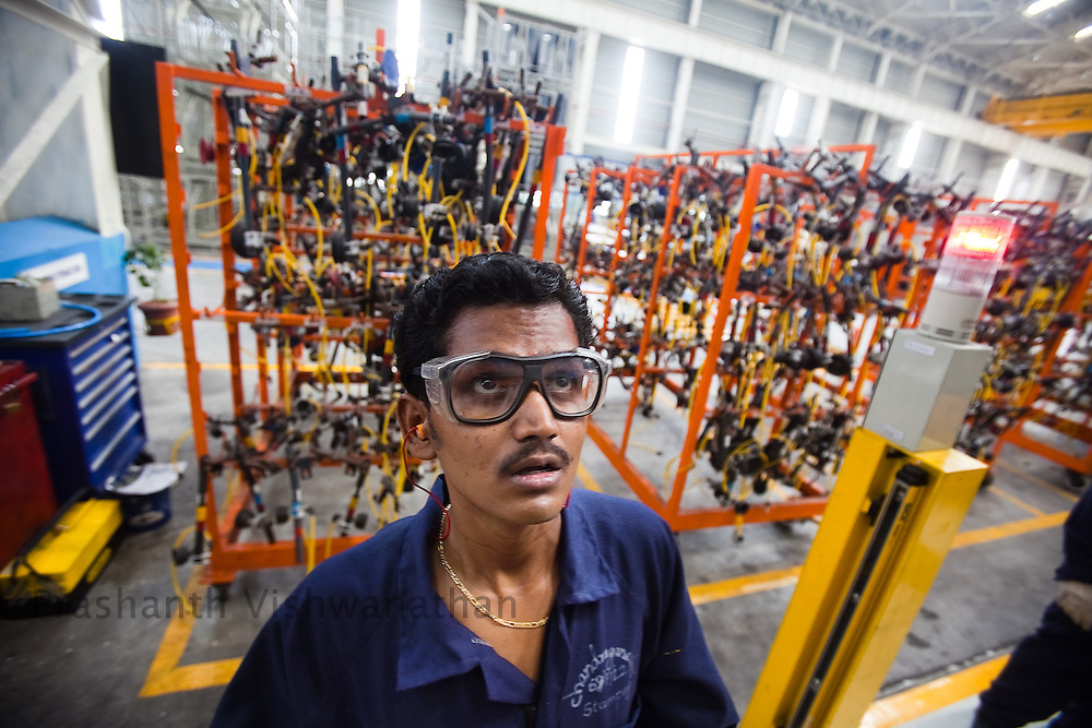 An employee works on a crane at the Ford Motor factory assembly line in the outskirts of Chennai, India, on Thursday, March 18, 2010. Photographer: Prashanth Vishwanathan/Bloomberg