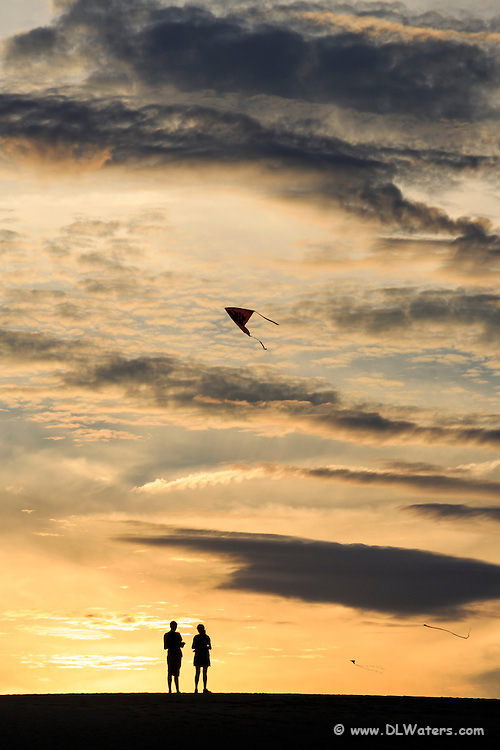 A couple flying a kite, silhouetted on Jockey's Ridge State Park against a cloudy  sunset sky.