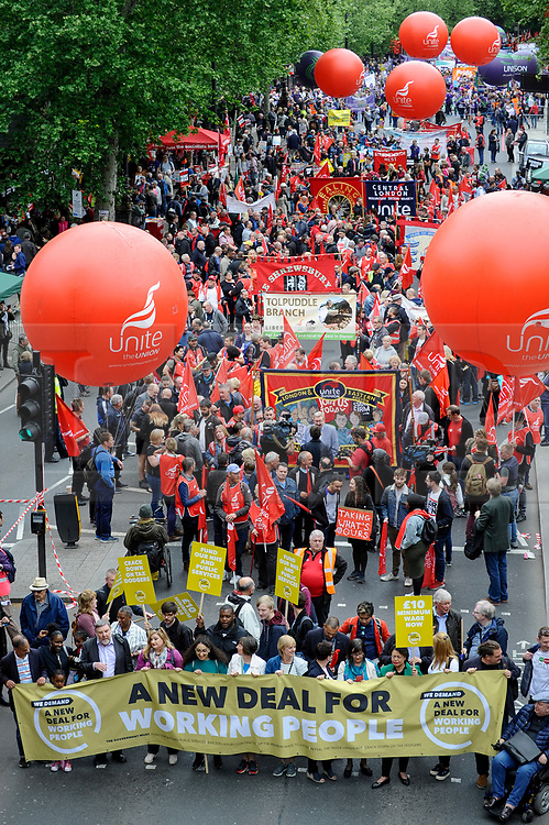 © Licensed to London News Pictures. 12/05/2018. LONDON, UK.  People stand behind a banner as thousands take part in a Trades Union Congress (TUC) march and rally, from Embankment to Hyde Park, calling for improved workers' pay and rights as well as improvement to pubic services.  Photo credit: Stephen Chung/LNP