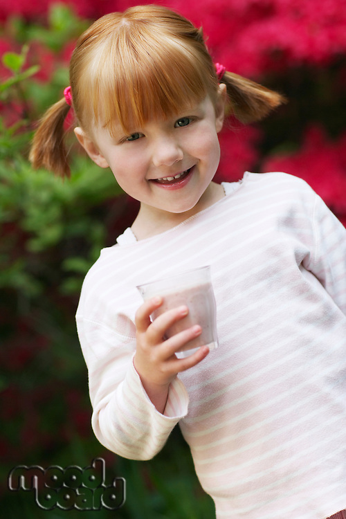 Portrait of young girl (5-6) with glass of smoothie smiling