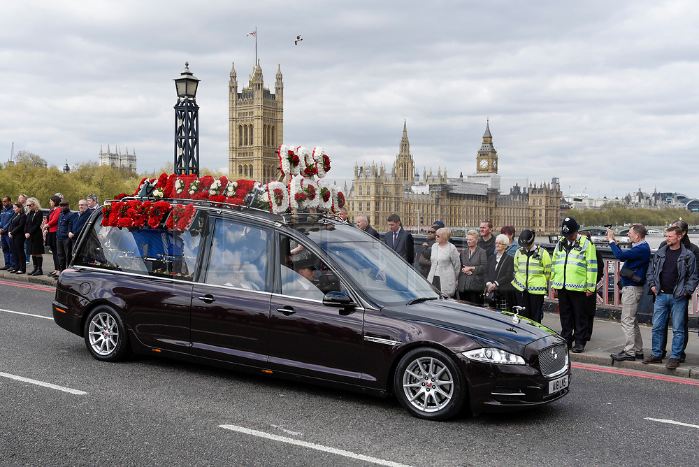 © Licensed to London News Pictures. 10/04/2017. London, UK. Mourners, including police officers, pay their respects as the hearse carrying the coffin of PC Keith Palmer passes by on Lambeth Bridge.  PC Palmer was killed in last month's attack in Westminster.  5,000 police officers have lined the funeral route from Westminster Abbey to Southwark Cathedral.   Photo credit : Stephen Chung/LNP