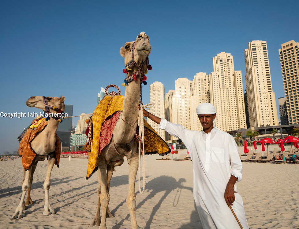 Man offering camel rides for tourists on beach at The Beach in Jumeirah Beach  district of modern Dubai, UAE, United Arab Emirates.