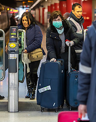 © Licensed to London News Pictures. 02/03/2020. London, UK. A passenger arrives on the Gatwick Express at Victoria Station in a protective mask and rubber gloves as fears of a pandemic increase after 4 new cases of Coronavirus are confirmed in the UK. Photo credit: Alex Lentati/LNP