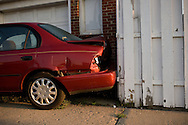 A wrecked car stands parked in front of a garage in Dearborn, Detroit. 2011