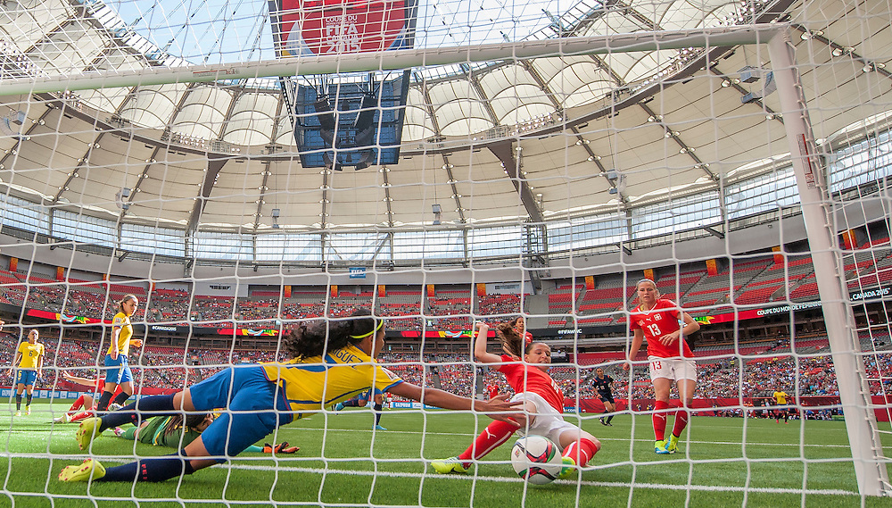 Ingrid Rodriguez of team Ecuador dives for the ball as Fabienne Humm of team Switzerland kicks the ball in for a goal in 2015 women's World Cup Soccer in Vancouver during the first round action between Switzerland and Ecuador