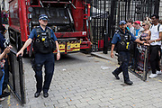 On the day that Britain's new Conservative Party Prime Minister, Boris Johnson enters Downing Street to begin his government administration, replacing Theresa May after her failed Brexit negotiations with the European Union in Brussels, armed police officers allow a refuse lorry to enter the gates of Downing Street, on 24th July 2019, in Westminster, London, England.