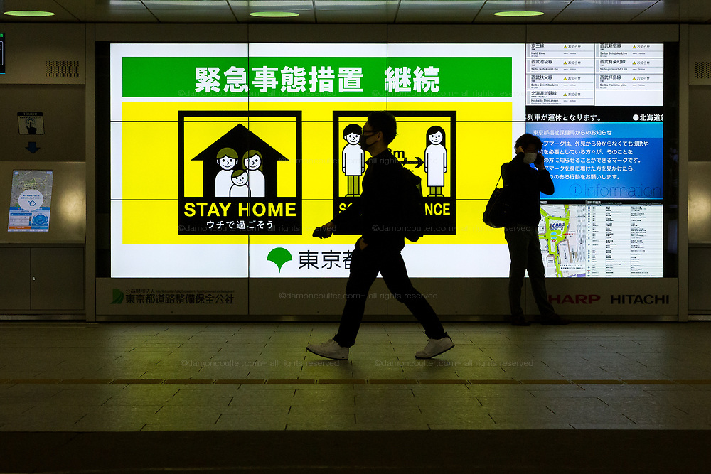 People walk past a sign advising people to stay home and maintain social distancing  against infection with the Coronavirus  in Shinjuku station,, Tokyo, Japan. Friday May 22nd 2020.. The two-month long state of emergency  declared by the Japanese government in response to the COVID-19 pandemic  is slated to end on May 25th Despite Japan appearing to have avoided the high infection and mortality rates of some countries. Areas in Tokyo and across the country have many businesses shuttered and closed and the streets are a lot quieter than usual.