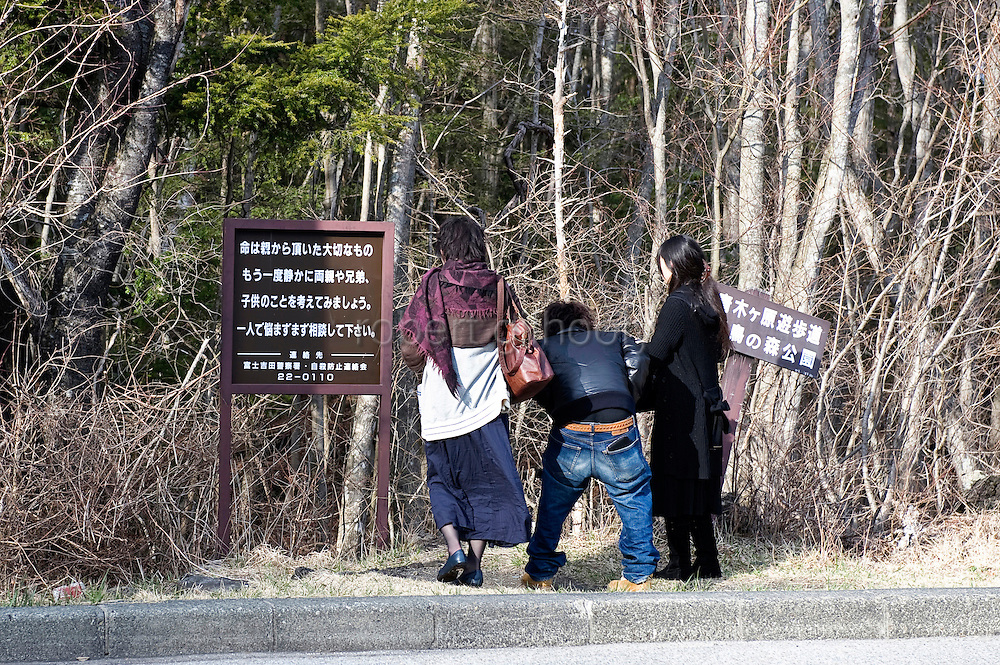 """Passerby look at a sign, which  was erected by a volunteer helpline and urges visitors considering suicide to """"calmly reconsider"""" their acts and talk over problems with family members, at the entrance of Aokigahara Jukai in Yamanashi Prefecture, Japan on 29 March 2009."""