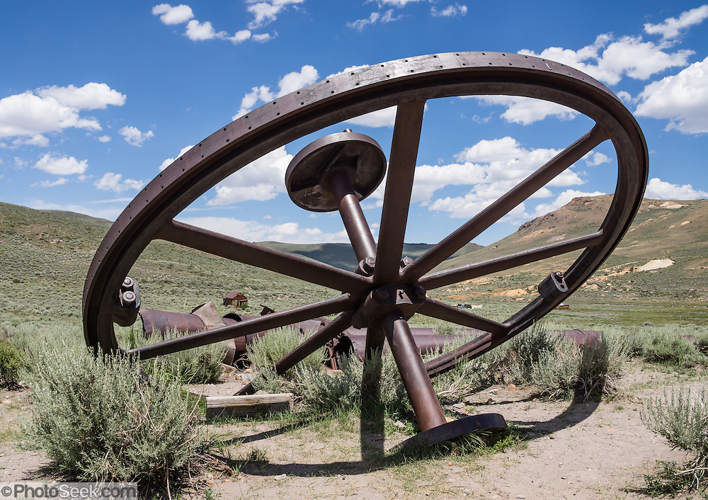 """A big, discarded mining flywheel rusts in a field at Bodie, California's official state gold rush ghost town. Bodie State Historic Park lies in the Bodie Hills east of the Sierra Nevada mountain range in Mono County, near Bridgeport, California, USA. After W. S. Bodey's original gold discovery in 1859, profitable gold ore discoveries in 1876 and 1878 transformed """"Bodie"""" from an isolated mining camp to a Wild West boomtown. By 1879, Bodie had a population of 5000-7000 people with 2000 buildings. At its peak, 65 saloons lined Main Street, which was a mile long. Bodie declined rapidly 1912-1917 and the last mine closed in 1942. Bodie became a National Historic Landmark in 1961 and Bodie State Historic Park in 1962."""