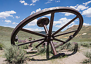 "A big, discarded mining flywheel rusts in a field at Bodie, California's official state gold rush ghost town. Bodie State Historic Park lies in the Bodie Hills east of the Sierra Nevada mountain range in Mono County, near Bridgeport, California, USA. After W. S. Bodey's original gold discovery in 1859, profitable gold ore discoveries in 1876 and 1878 transformed ""Bodie"" from an isolated mining camp to a Wild West boomtown. By 1879, Bodie had a population of 5000-7000 people with 2000 buildings. At its peak, 65 saloons lined Main Street, which was a mile long. Bodie declined rapidly 1912-1917 and the last mine closed in 1942. Bodie became a National Historic Landmark in 1961 and Bodie State Historic Park in 1962."