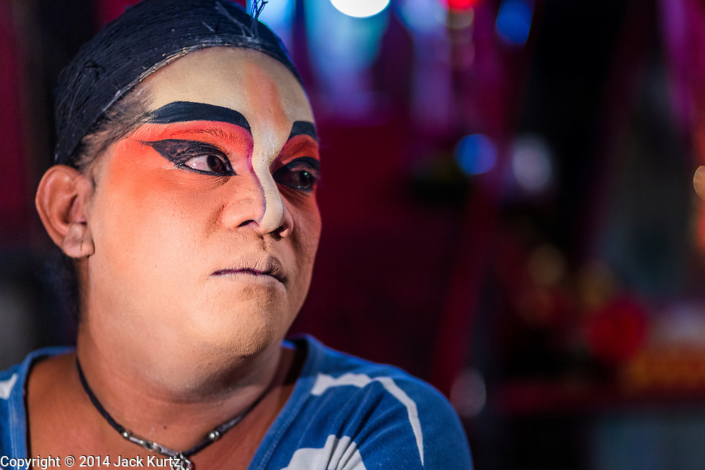 "25 JANUARY 2014 - BANG LUANG, NAKHON PATHOM, THAILAND: A performer with the Sing Tong Teochew opera troupe before a show in a Chinese shrine in the town of Bang Luang, Nakhon Pathom, Thailand. The Sing Tong Teochew opera troupe has been together for 60 years and travels through central Thailand and Bangkok performing for mostly ethnic Chinese audiences. Chinese opera was once very popular in Thailand, where it is called ""Ngiew."" It is usually performed in the Teochew language. Millions of Chinese emigrated to Thailand (then Siam) in the 18th and 19th centuries and brought their cultural practices with them. Recently the popularity of ngiew has faded as people turn to performances of opera on DVD or movies. There are still as many 30 Chinese opera troupes left in Bangkok and its environs. They are especially busy during Chinese New Year when travel from Chinese temple to Chinese temple performing on stages they put up in streets near the temple, sometimes sleeping on hammocks they sling under their stage.     PHOTO BY JACK KURTZ"