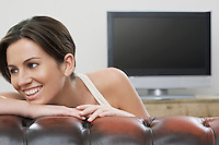Young woman on sofa in front of flat screen television