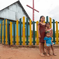 Three young girls pose in front of the colorful church in the small community of San Francisco de Loreto on the Marañon River in the Peruvian Amazon.