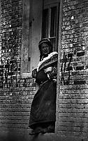 Tibetan nomad woman standing in a doorway in Langmusi, China.