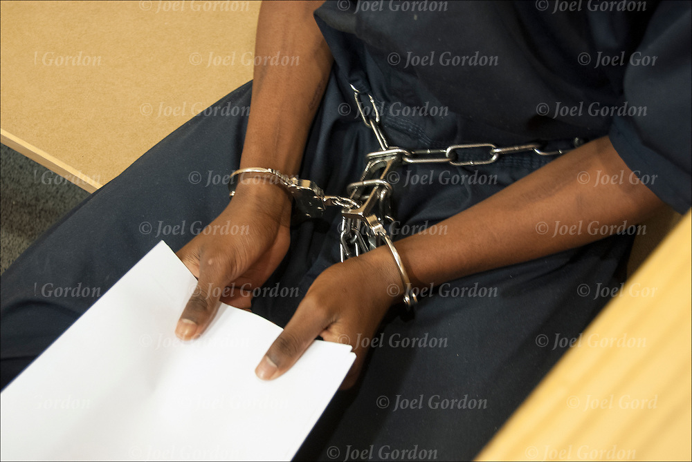 African American juvenile male in handcuffed sitting in the Juvenile Justice Center waiting for judge to hear his case, holding his court papers.