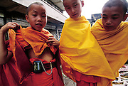 "As a preadolescent Buddhist monk walks through a market with two other young monk friends in the southern province of Yunnan; he proudly displays his fake pager; a coveted toy from ""Motorora; Ching Menghan Sunday Market; Yunnan; China. (Man Eating Bugs page 84; 85)"