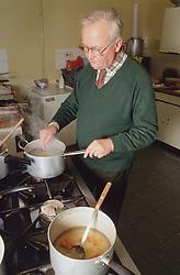 Elderly man cooking in day centre kitchen,