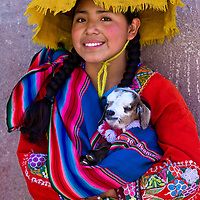"CUSCO , PERU - MAY 28 : Unidentified Peruvian girl in traditional colorful clothes holding a lamb in here arms in the "" Unesco world heritage"" city ""Cusco"" on May 28 2011"
