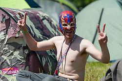 © Licensed to London News Pictures. 11/06/2015. Newport, UK. A  mask-wearing festival goer at the Isle of Wight Festival 2015 jjust after being allowed onto the campsite at midday. This years festival include headline artists the Prodigy, Blur and Fleetwood Mac.  Photo credit : Richard Isaac/LNP
