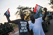 BANJUL, GAMBIA - JAN 22: Civilians wave Gambian flags in front of armoured ECOWAS vehicles as thety stand on the side of the route ahead of taking Banjul on 22 January 2017 in Banjul, Gambia.