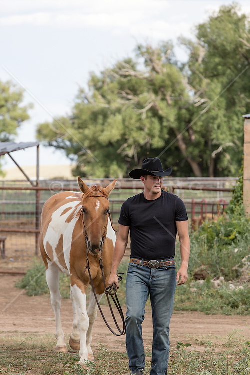 rugged cowboy walking with a horse on a ranch