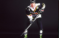 1997:  Pro roller hockey player Tony Szabo in ready position for V-Formation skates during a studio photo shoot.  Skater wearing skates, pants, uniform, stick helmet, gloves ready to play sport. Transparency slide scan.
