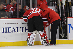 Oct 13; Newark, NJ, USA; A New Jersey Devils trainer checks on New Jersey Devils goalie Martin Brodeur (30) after he dove to the ice making a save during the first period at the Prudential Center.