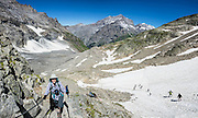 Lötsch glacier trail, Lötschen Pass. Bern canton, Switzerland, the Alps, Europe. Kandersteg is a great base for hiking in Switzerland. An epic hike from Selden in Bern canton traverses Lötsch glacier and Lötschen Pass (German: Lötschenpass, Swiss German: Lötschepass) to neighboring Lötschental in Valais canton; hiking poles recommended. The walk starts with a reserved Postbus ride from Kandersteg to Selden (in Gasterntal / Gasteretal / Gasterental), climbs 1350 meters, descends 925 m, and ends 13 km later at Lauchernalp lift station, which descends to Wiler in Lötschental, to reach Goppenstein via Postbus, back to Kandersteg via train. You can also reverse the route or stay overnight in dorms at Lötschepass hut. This image was stitched from multiple overlapping photos.