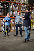 01/14/2016 132514 -- Garland, TX -- &copy; Copyright 2016 Mark C. Greenberg<br /> <br /> From left: President and COO Rick Sukkar and CEO Alex Keechleof talk with warehouse manager Kevin Sadler in the warehouse of Garland, Texas based Monster Moto