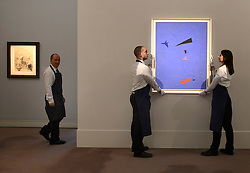 "© Licensed to London News Pictures. 14/06/2012. London, UK Gallery technicians hold Joan Miro's painting ""Peinture' which is estimated to fetch 15-20MillionGBP. Photocall for Sotheby's June Impressionist and Modern Art Sale this June. Photo credit : Stephen Simpson/LNP"