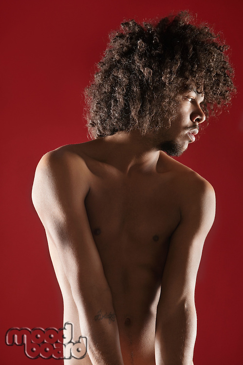 Young man standing naked while looking away over colored background