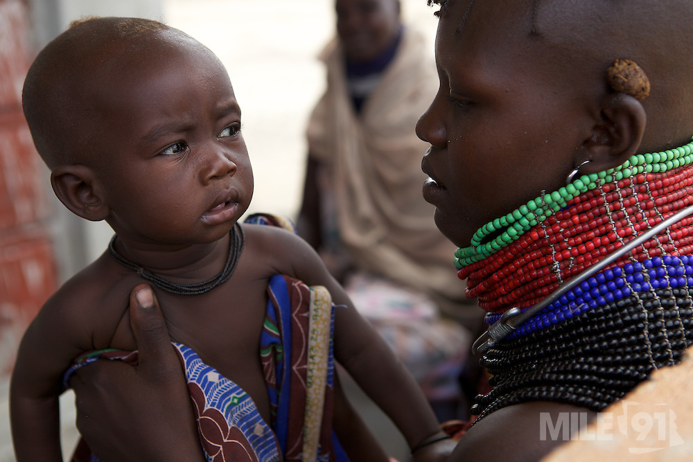 Women meet under a tree with their babies at the Kakimat outreach site. ..These clinics provide immunisations and nutrition support and advice...The women walk for miles to visit these clinics.