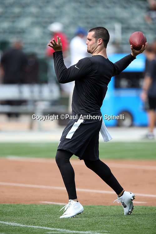 Oakland Raiders quarterback Derek Carr (4) throws a pregame pass before the 2015 NFL week 1 regular season football game against the Cincinnati Bengals on Sunday, Sept. 13, 2015 in Oakland, Calif. The Bengals won the game 33-13. (©Paul Anthony Spinelli)