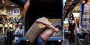 Wufenpu Fashion District night-time market, Taipei, Taiwan.  Clothing delivery by truck in narrow alley with man hefting large carton on his back.