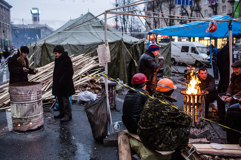 KIEV, UKRAINE - DECEMBER 13: Anti-government protesters keep warm around fires in the middle of a street leading to Independence Square, which they have occupied for more than three weeks, on December 13, 2013 in Kiev, Ukraine. Thousands of people have been protesting against the government since a decision by Ukrainian president Viktor Yanukovych to suspend a trade and partnership agreement with the European Union in favor of incentives from Russia. (Photo by Brendan Hoffman/Getty Images) *** Local Caption ***