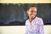 Local teacher Rebecca Ngovano sitting in front of a blackboard in one of the classrooms of Angaza school, Lindi, Tanzania